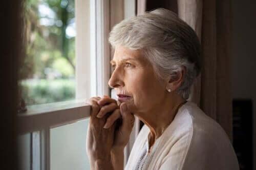 Demansı olan yaşlı bir kadın pencereden bakıyor.