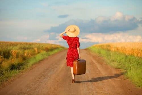 Elinde bavulu ile yolda yürüyen bir kadın.