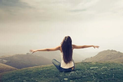 Bir dağın tepesinde kollarını açmış, yerde oturan, kameraya sırtı dönük bir kadın.