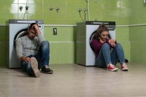 Ayrı çamaşır makinelerine sırtlarını yaslamış, yerde oturan iki kişi.