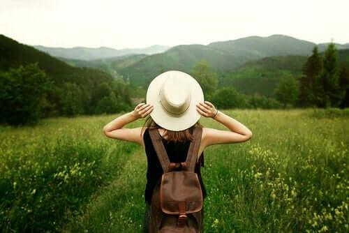 Yeşil bir alanın ortasında kameraya sırtı dönük şapkasını tutarak duran bir kadın.