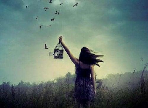 Elindeki kafesteki kuşları serbest bırakan bir kadın.