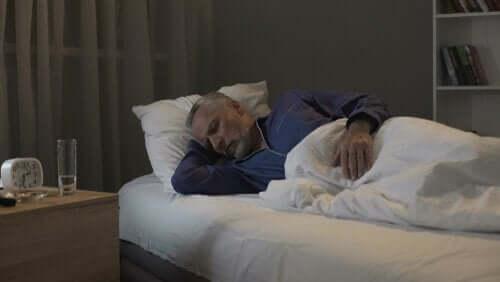 Yatağına yatmış uyuyan yaşlı bir adam.