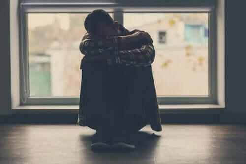 Kendisine sarılmış bir şekilde yerde oturan bir adam.