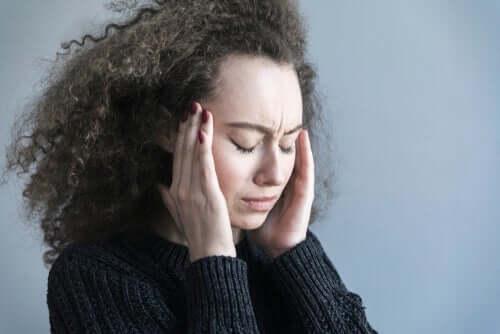 Baş ağrısı çeken, başını ellerinin arasına almış duran bir kadın.