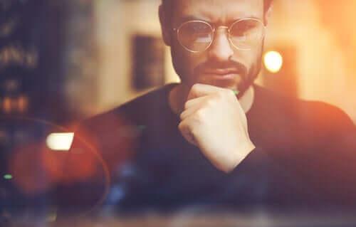 Gözlüklü adam kafeteryada düşünüyor