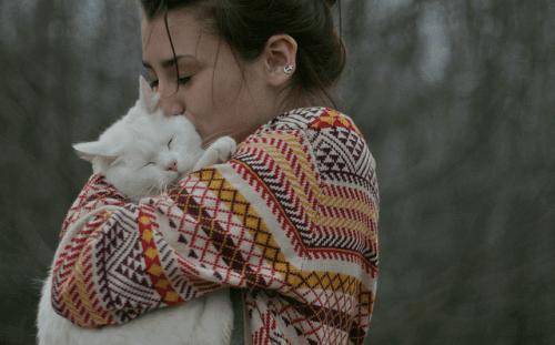 Bir kediyi kucaklamış, öpen bir kadın.