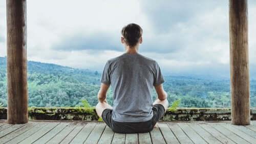 Dağ manzarasına karşı meditasyon yapan bir adam.