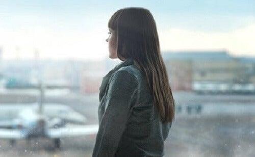 Pencereden uzaklara bakmakta olan bir kadın.