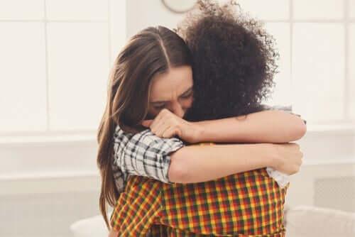 Birbirlerine sarılmakta olan iki kişi.
