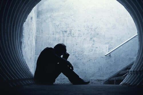 Bir tünelin içinde yerde oturan bir adam.