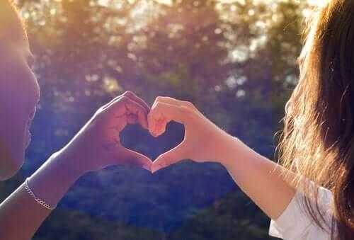 elleriyle kalp işareti yapan iki dost