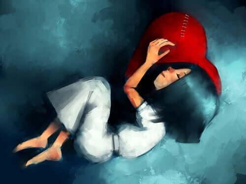 Bir kalbin üstüne yatmış uyuyan kız çizimi.