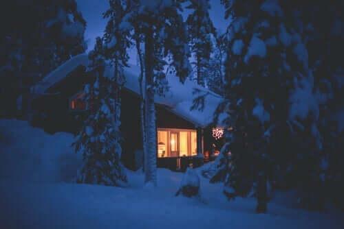 Karlar ile kaplanmış, ışıkları açık bir kulübe.