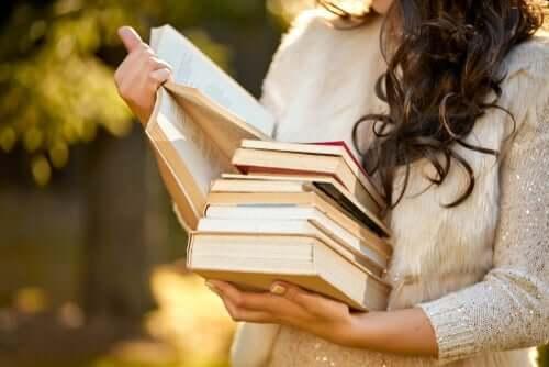 Elinde bir sürü kitap tutan, kitaplardan birini okuyan bir kadın.