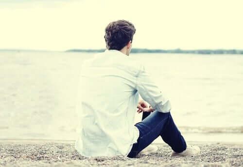 Kumsalda oturan adam