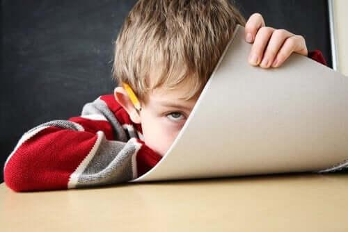 tahta önünde defterinin arkasına saklanan çocuk
