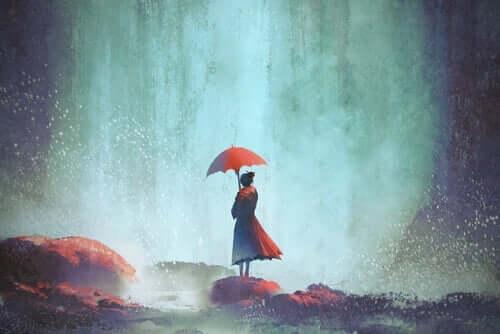 Yağmurda kayaların üstünde şemsiyeyle duran kadın
