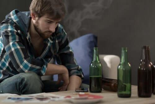 Önünde alkol içeren şişeler ile oturan bir adam.