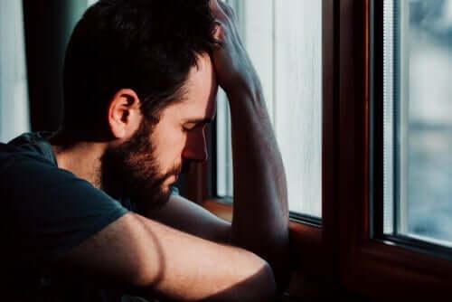 Pencerenin önünde durmuş başını tutan bir adam.