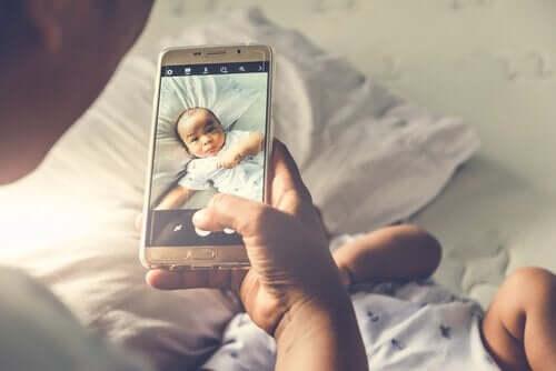 uzanan bebeğin fotoğrafını çeken ebeveyn