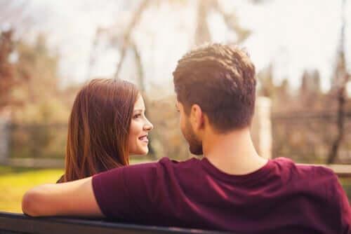 Bir bankta oturmuş birbirlerine bakan bir çift.