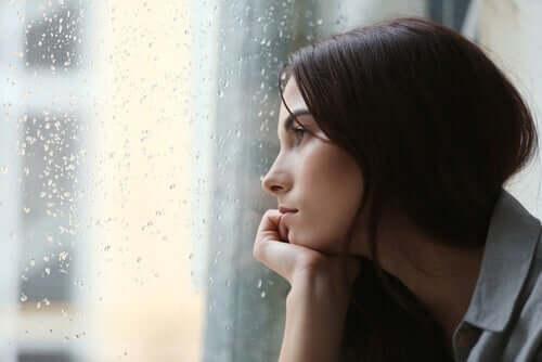 Dışarıda yağmur yağarken camın önünde oturan bir kadın.