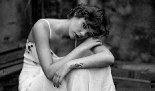 Beyaz elbiseli, üzgün görünen bir kadın.
