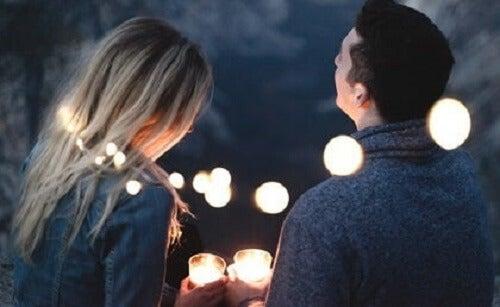 Kameraya arkaları dönük bir şekilde bazı ışıkların önünde konuşan bir kadın ve bir adam.