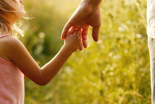 Annesinin elini tutan küçük bir kız çocuğu.