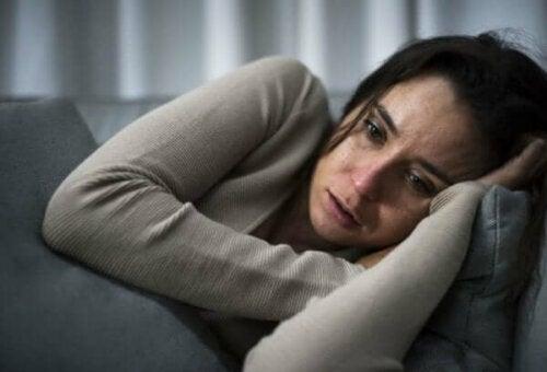 Koltukta yatmış ağlayan bir kadın.