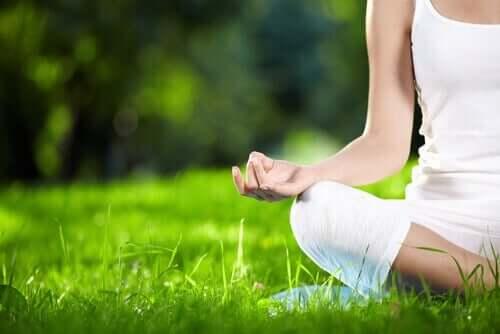 Çimenlere oturmuş meditasyon yapan bir kadın.
