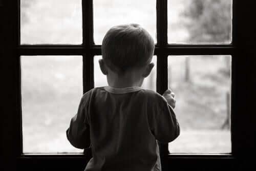 Pencereden bakan bir çocuğun siyah beyaz bir resmi.