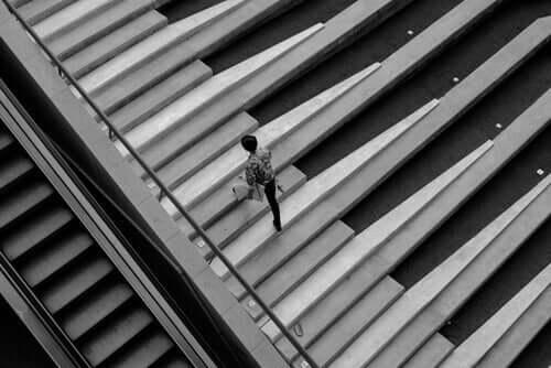 Piyano tuşları gibi görünen merdivenlerden çıkan bir kişi.