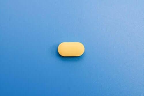 Mavi zamin üzerinde duran sarı bir ilaç.
