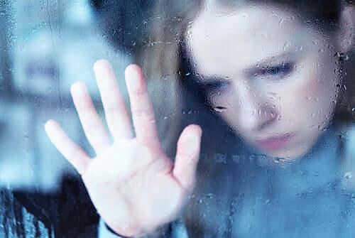 Üzgün kadın elini cama yaslamış