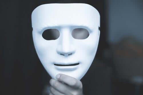 Elinde beyaz maske tutan adam