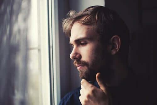 Eli çenesinde düşünerek camdan dışarı bakan erkek