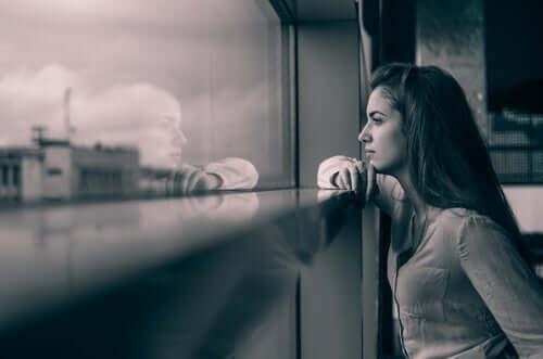 camdan dışarıya bakan hüzünlü kadın