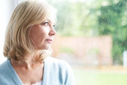 Orta yaşlı kadın pencereden dışarı bakarken belki de çaresizlik duygusunu yaşıyor