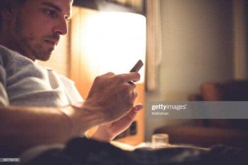 Yatağında telefonunu kullanan bir adam.