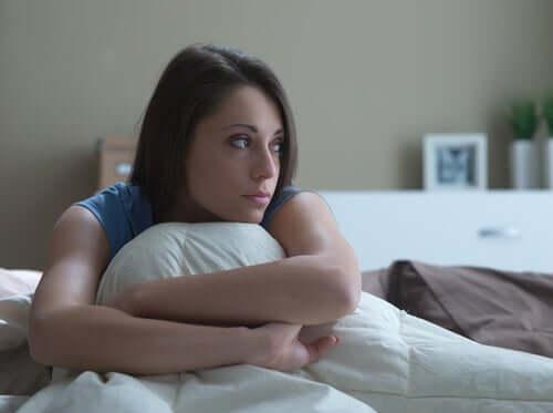 Yastığına sarılmış, üzgün görünen bir kadın.