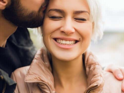 Bir kadını şakağından öpen bir adam.