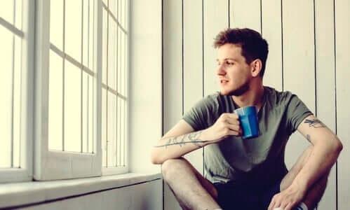 Elinde kahve kupasını tutan bir adam.