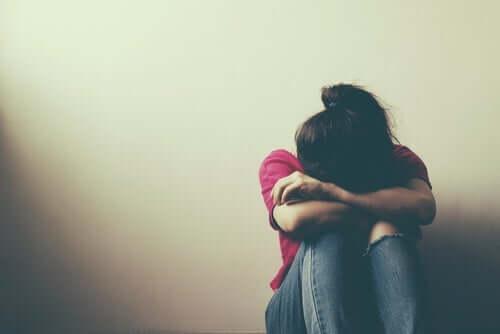 Duvarın önünde dizine kapanmış ağlayan kadın