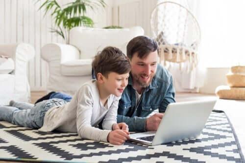 Laptop üzerinde bir şeylere bakan bir baba ve oğlu.