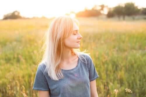 Doğanın ortasında gözleri kapalı duran, mutlu görünen bir kadın.