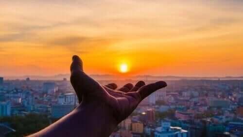Elini batan güneşe uzatmış bir kişi.