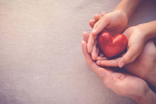 Bir yetişkin ve bir çocuğun ellerinin içerisindeki bir kalp.