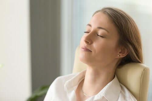 Gözlerini kapatmış bir şekilde oturan bir kadın.